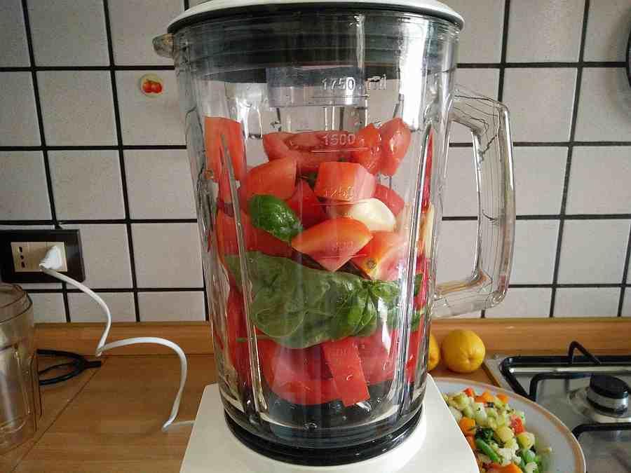 Pomodori per il sugo con basilico nel frullatore